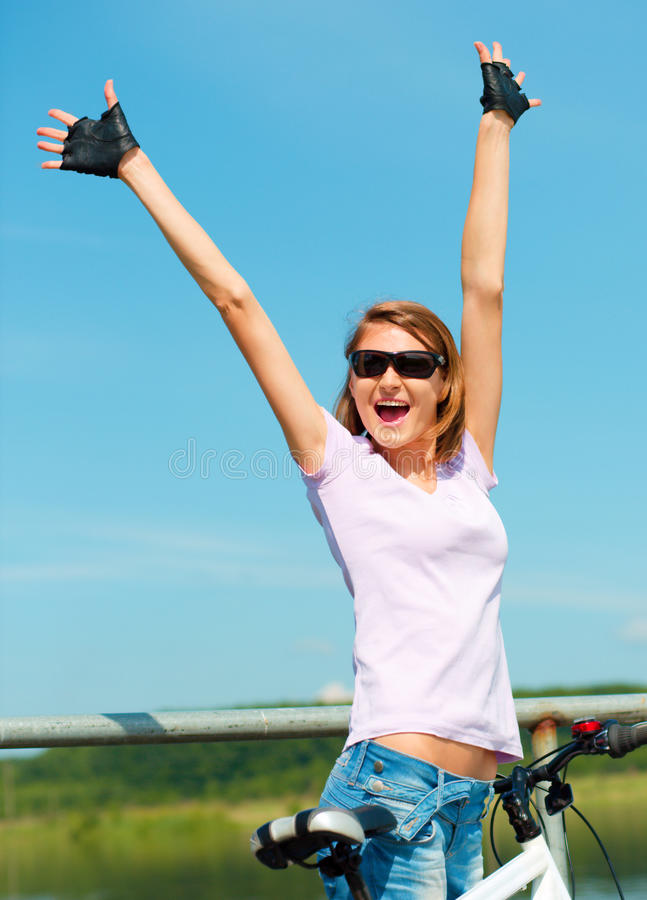 Young woman raised her hands up in joy. Young happy woman raised hands up in joy, outdoor shoot stock image