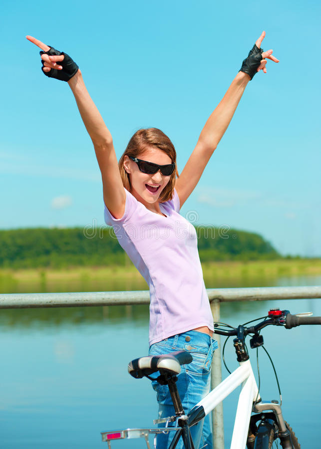 Young woman raised her hands up in joy. Young happy woman raised hands up in joy standing behind her bicycle, outdoor shoot royalty free stock images