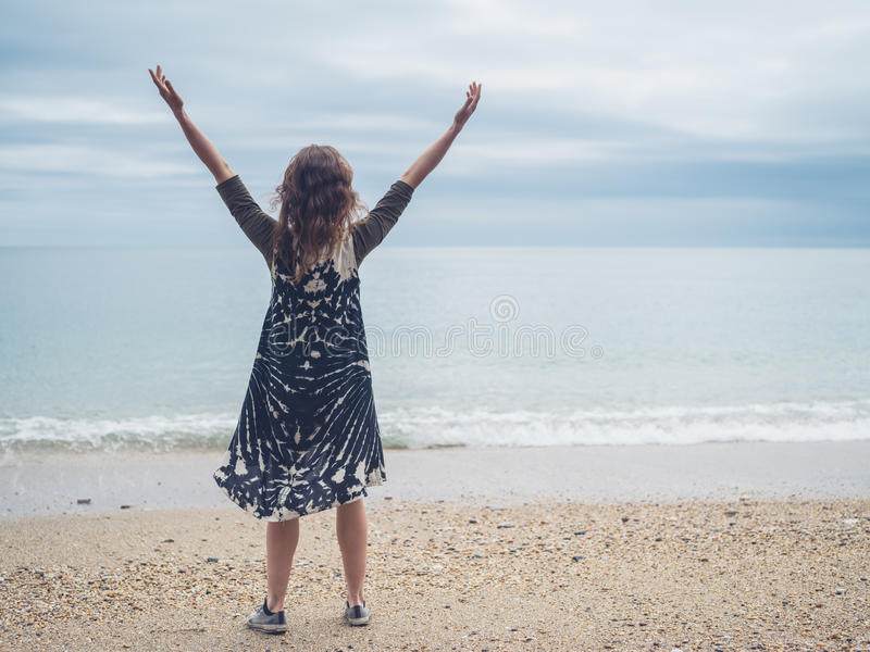 Young woman raising her arms on the beach. A young woman is raising her arms on the beach by the sea royalty free stock image