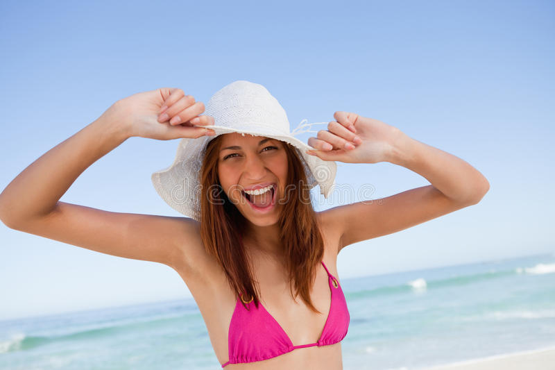 Young woman raising her arms in happiness in front of the sea stock photo