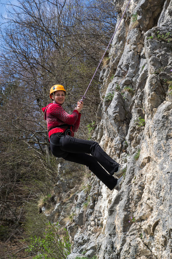 Young woman rappelling. Young woman with helmet rappelling on a rocky wall royalty free stock photography