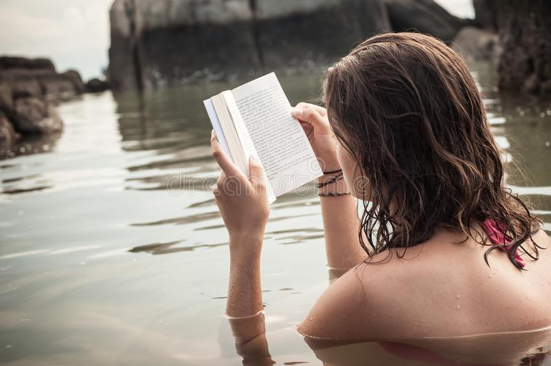 Young woman read book during beach vacation royalty free stock image