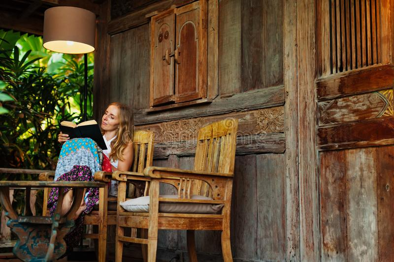 Young woman read paper book on outside veranda. Attractive girl sit on open-air veranda of wooden bungalow with tropical garden view, read romance in paper book stock image