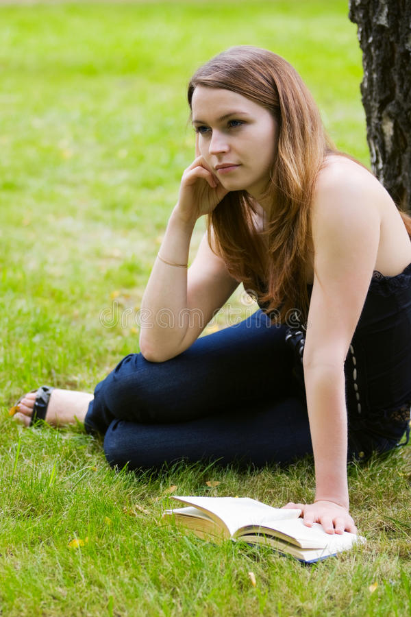 Young fashion woman reading a book outdoor stock photography
