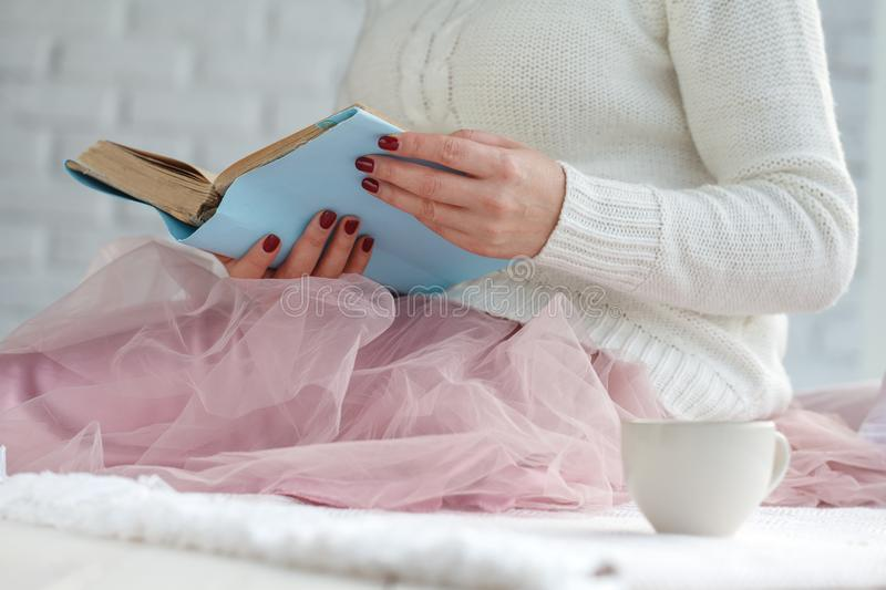 Young woman reading book and basking with plaid and coffee stock images