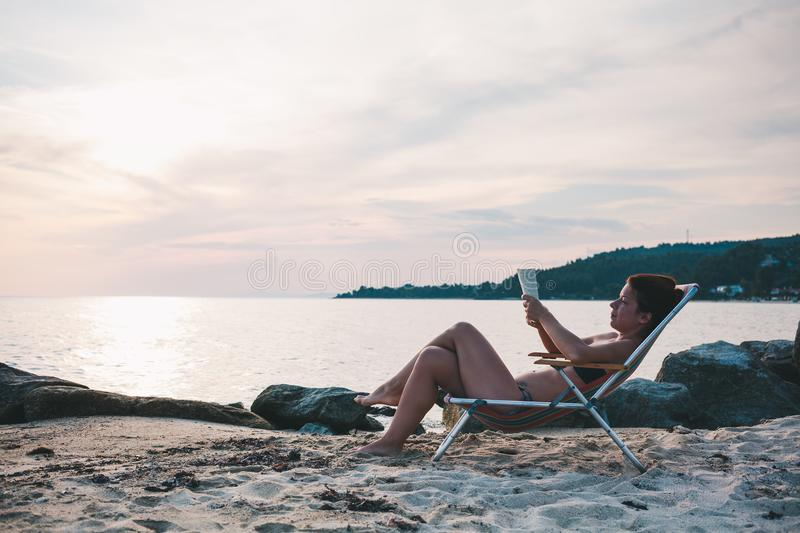 Young woman reading a book on the beach royalty free stock photography