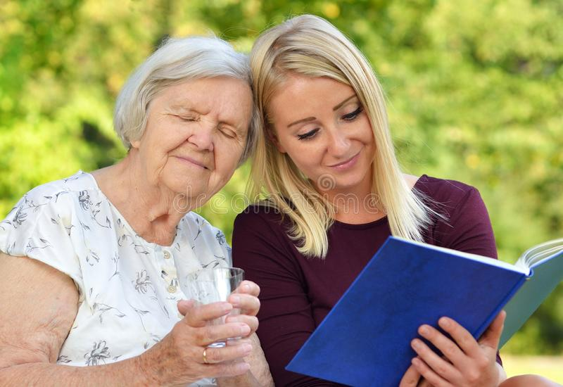 Young woman reading a book elderly woman. stock photo