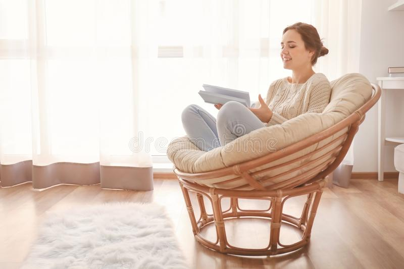 Young woman reading book on lounge chair at home stock photos