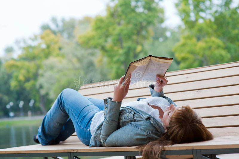 Young woman reading a book lying on the bench stock photo