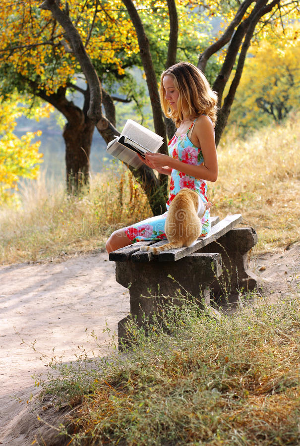 Young Woman Reading A Book. Near It Is The Cat Stock Photos