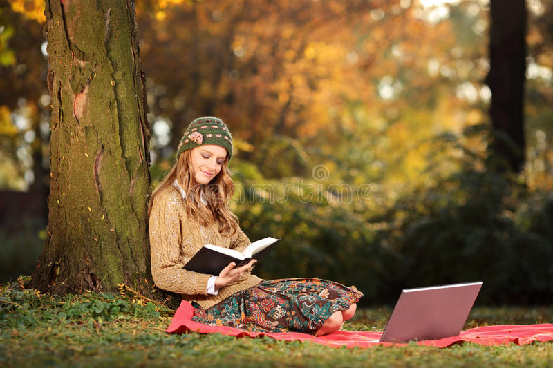 Download Young Woman Reading A Book In A Park Stock Photo - Image of novel, person: 22123834