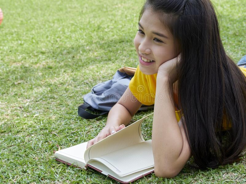 Young woman reading book in the park stock images