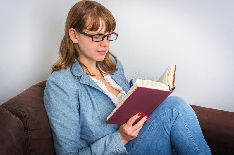 Young woman reading a book and sitting on the sofa royalty free stock photography