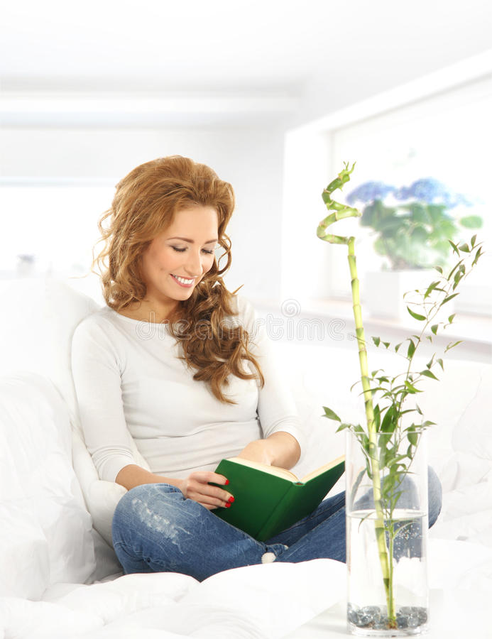 A young woman reading a book on the sofa stock photography