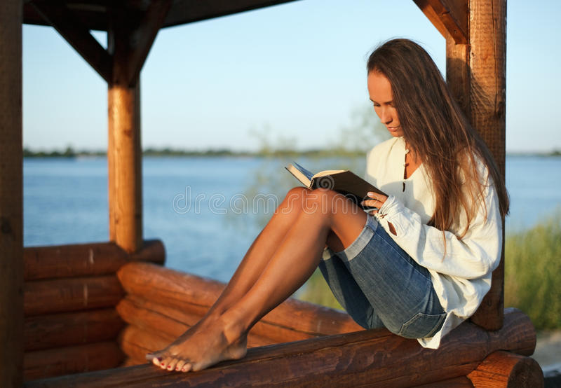 Download Young Woman Reading Book On Sunset Stock Photo - Image: 10718490