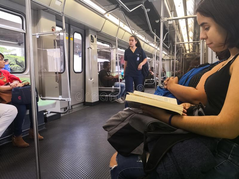 Young woman reading a book while traveling inside the Metro of Medellin stock photo