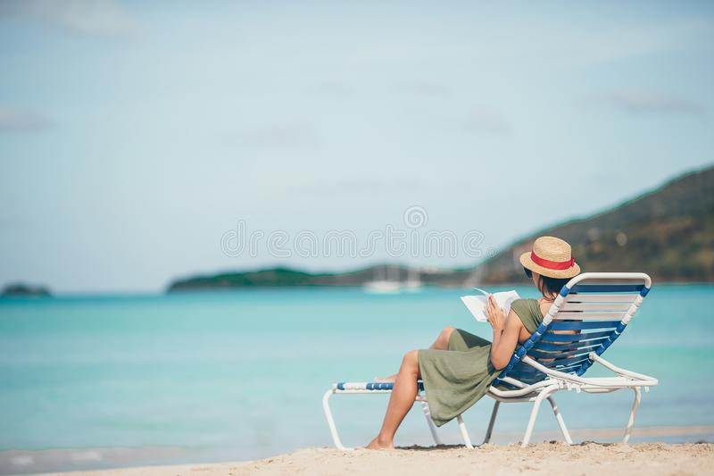 Young woman reading book on chaise-lounge on the beach royalty free stock photos