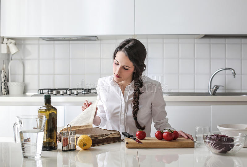 Download Young Woman Reading A Cook Book Stock Photo - Image of table, glass: 39500584