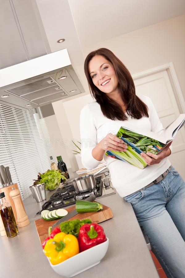 Young woman reading cookbook in the kitchen stock image