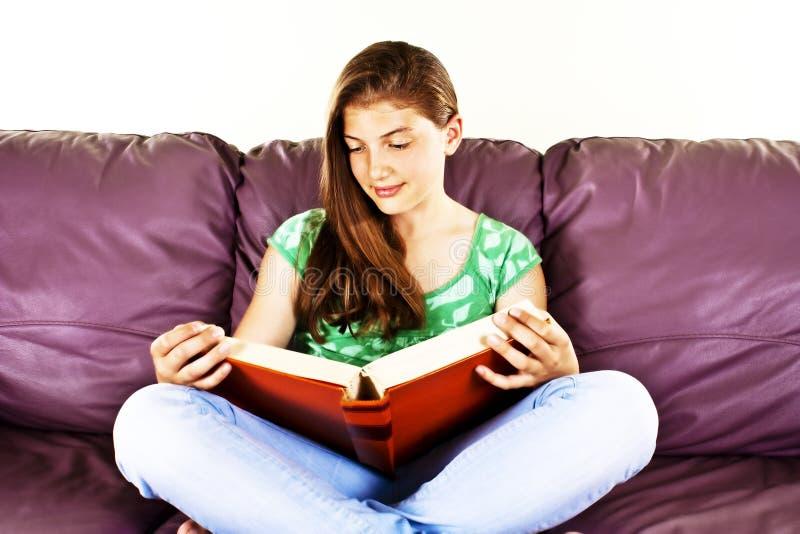 Young woman reading cross-legged on a sofa