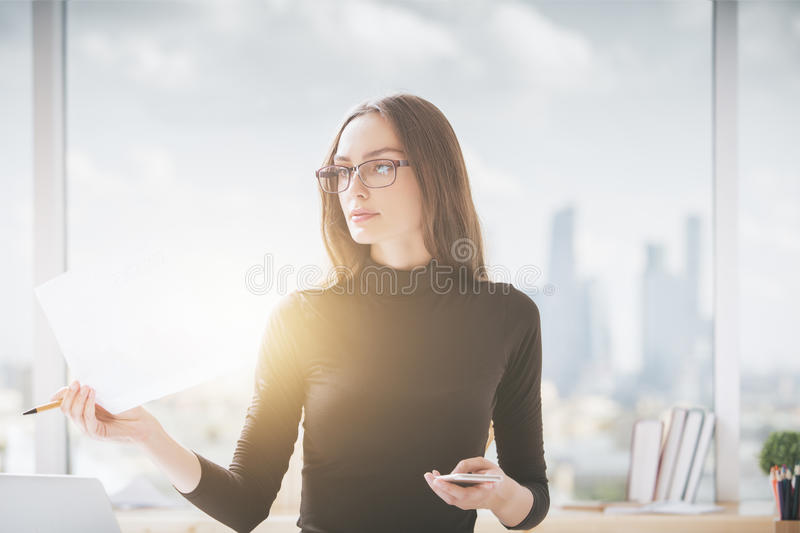 Young woman reading documentation. Portrait of attractive young woman with smartphone in hand reading documentation in office with city view and sunlight stock photography