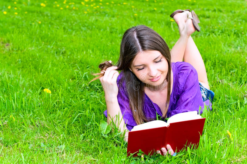 Young woman reading on the grass. Pretty young caucasian woman reading book on the summer meadow royalty free stock images