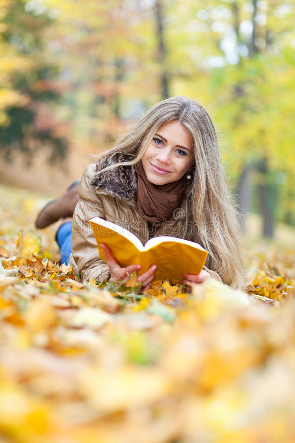 Free Young Woman Reading Lying On Leaves Royalty Free Stock Photo - 27820435