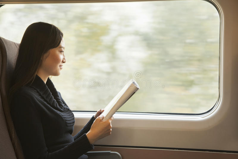 Young Woman Reading a Magazine While Riding the Train royalty free stock photography