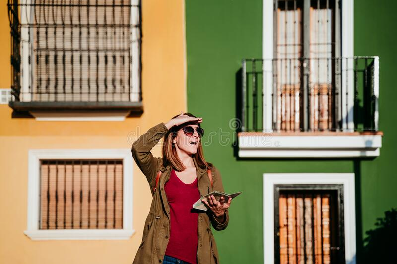 young woman reading a map over yellow and green background. travel concept royalty free stock photo