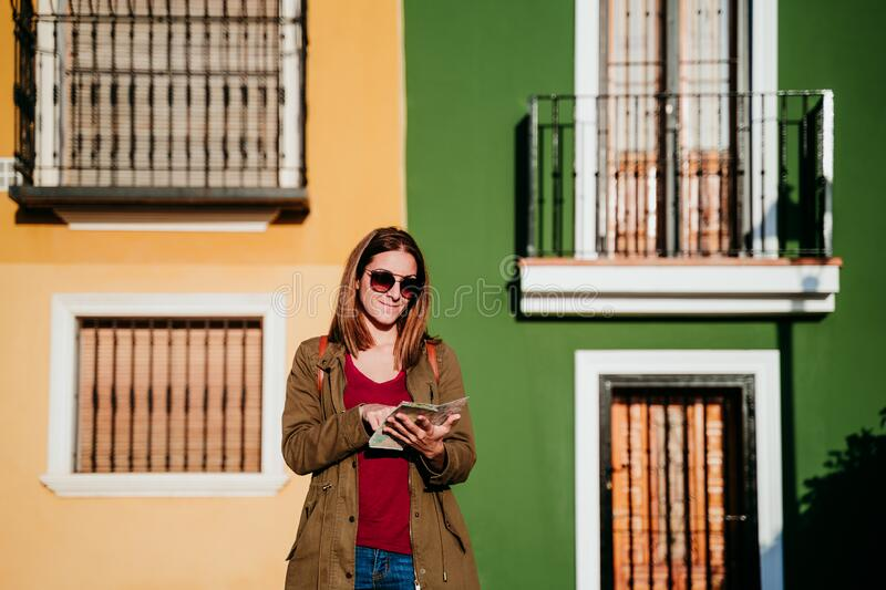 young woman reading a map over yellow and green background. travel concept stock image