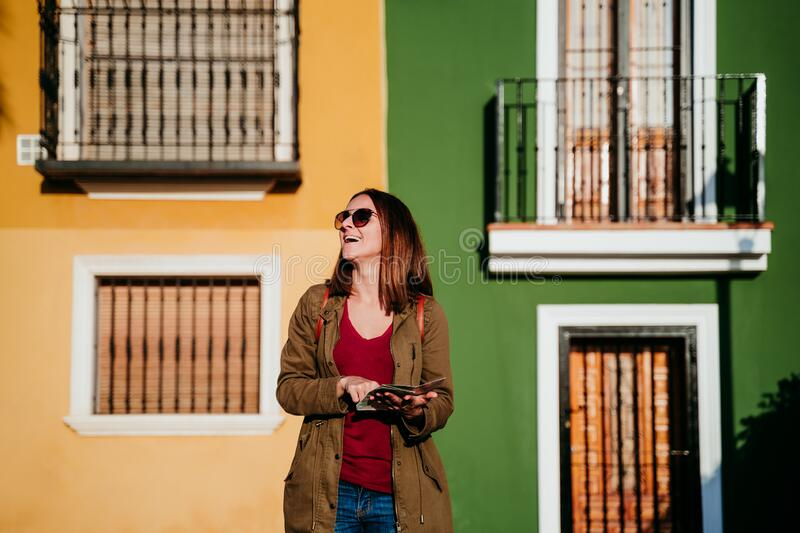 young woman reading a map over yellow and green background. travel concept stock photography