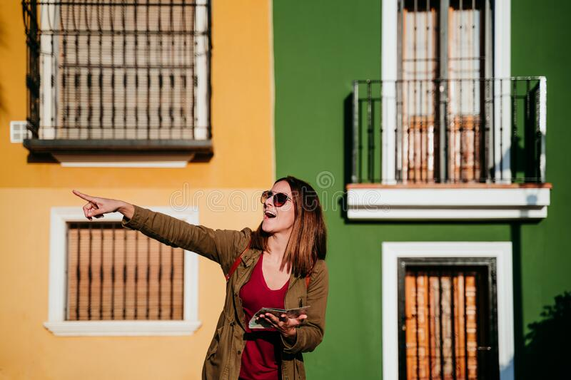 young woman reading a map over yellow and green background. travel concept royalty free stock image
