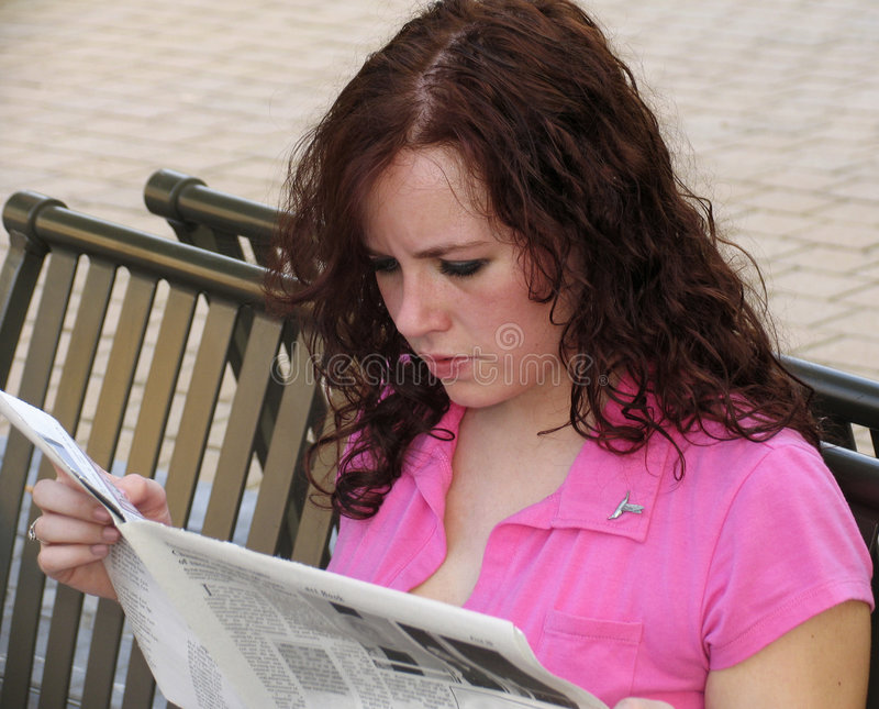 Young woman reading newspaper stock photography