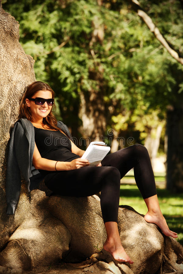 Young Woman Reading In The Park Stock Photo