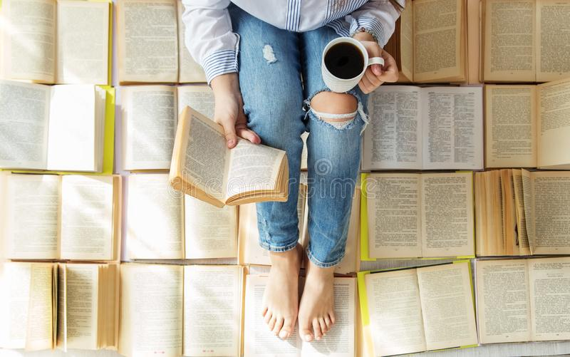 A young woman reads a book and drinks coffee. A lot of books. Concept for World Book Day, lifestyle, study, education.  stock photo