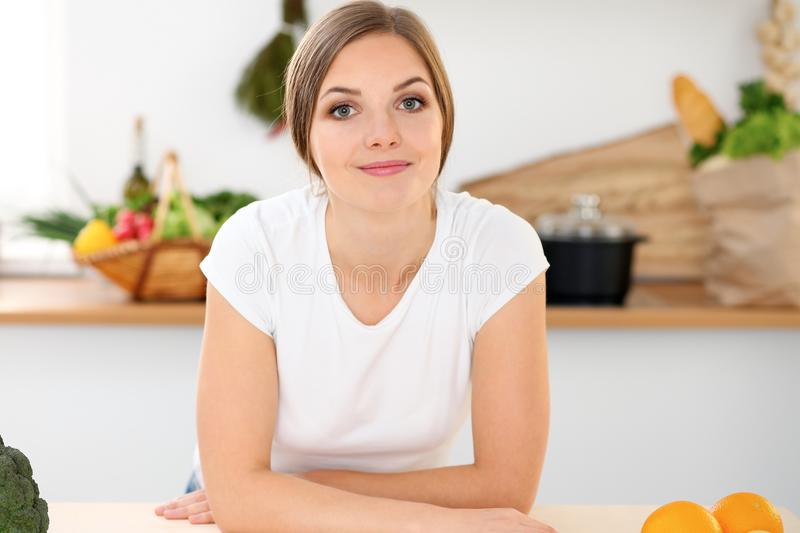 Young woman is ready for cooking in a kitchen. Housewife sitting at the table and looking at the camera. Young woman is ready for cooking in a kitchen stock photography