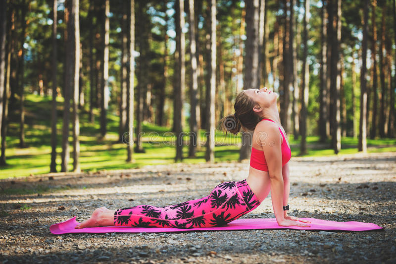 Young woman ready to practicing yoga in a forest. Upward Facing Dog Pose. Mind and body happiness concept stock photo