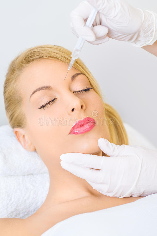 Young woman receiving botox injection in forehead. Young woman receiving botox injection between eybrows in beauty salon royalty free stock images