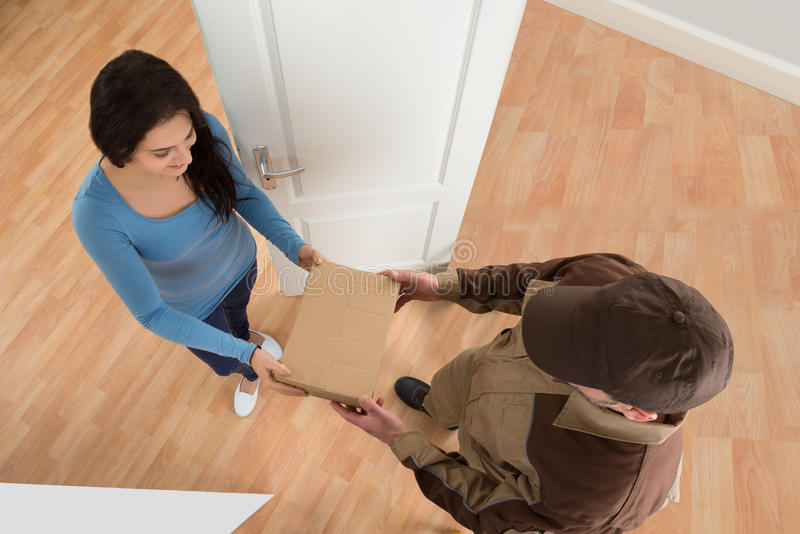 Young woman receiving courier from delivery man. Happy Young Woman Receiving Courier From Delivery Man At Home royalty free stock photos