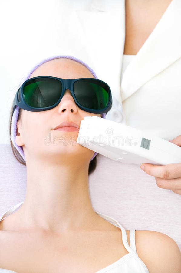 Young woman receiving epilation laser treatment stock image