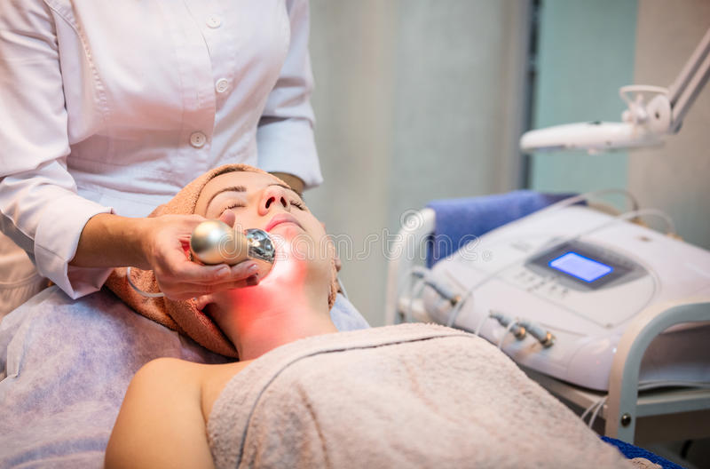 Young woman receiving facial treatment royalty free stock photography