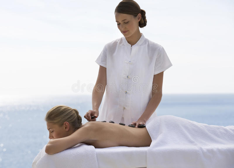 A young woman receiving a hot stone holistic treatment. A young women receiving a hot stone holistic treatment stock photography