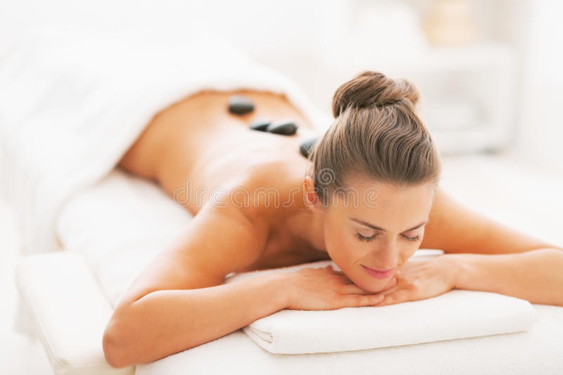 Young woman receiving hot stone massage. In spa salon stock image