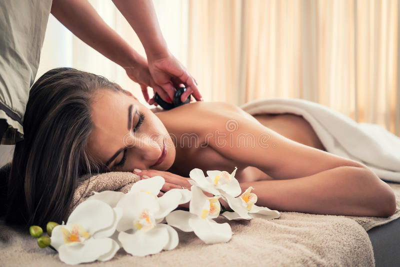 Young woman receiving hot stone massage at spa and wellness cent stock images
