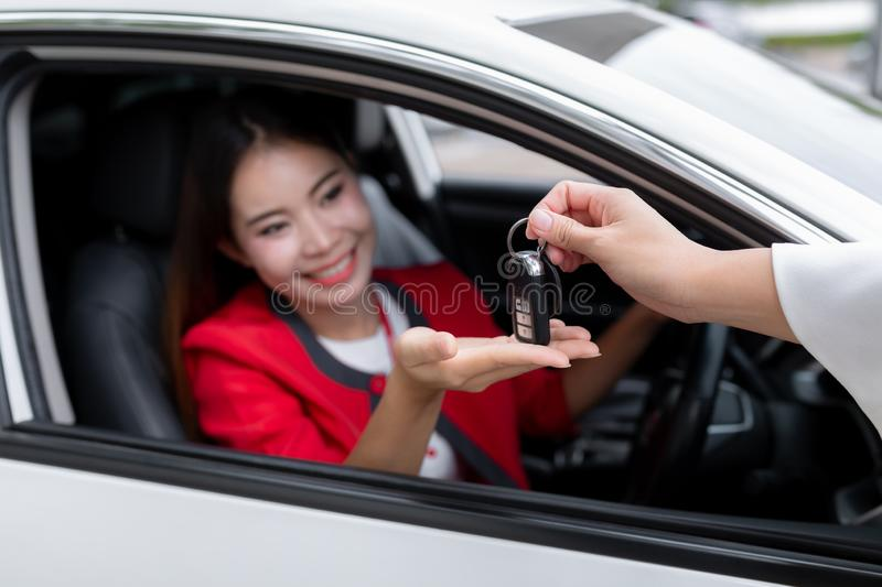 Young woman receiving the keys of her new car, Photo of happy yo royalty free stock image
