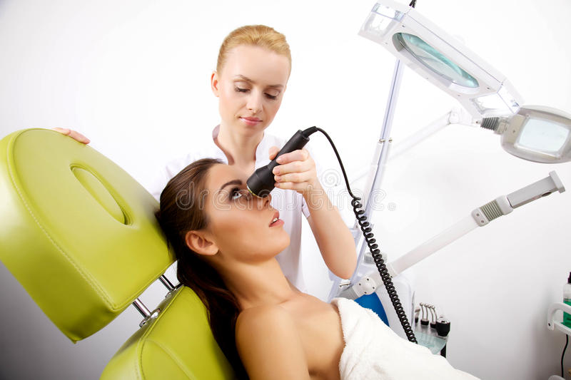 Young woman receiving laser therapy stock image