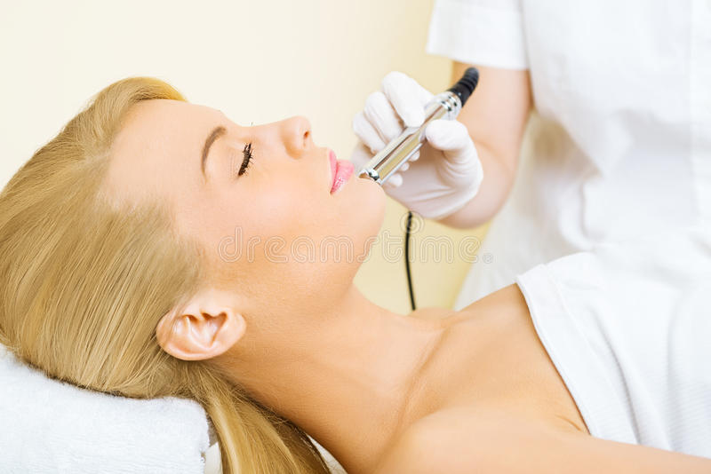 Young woman receiving microdermabrasion treatment. Beautiful blonde woman receiving microdermabrasion treatment in beauty salon stock images
