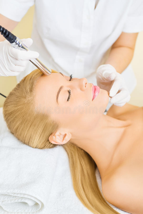 Young woman receiving microdermabrasion treatment. Beautiful blonde woman receiving microdermabrasion treatment in beauty salon stock photo
