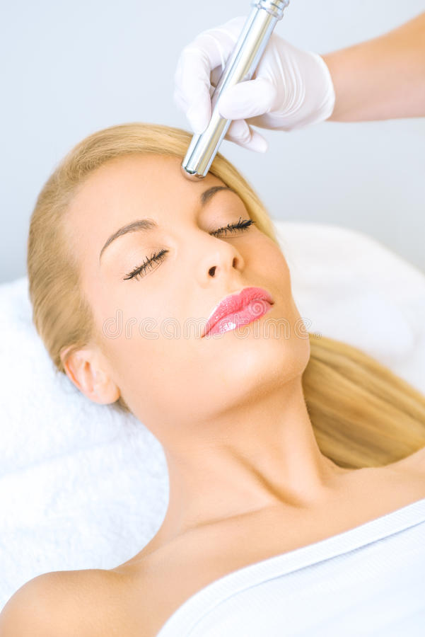 Young woman receiving microdermabrasion treatment. In beauty salon stock images