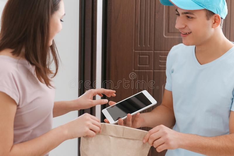 Young woman receiving order from courier. Food delivery service. Young women receiving order from courier. Food delivery service stock image